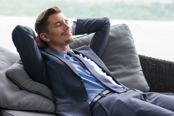Portrait of smiling handsome young businessman with his hands behind head lying on couch, dozing, relaxing